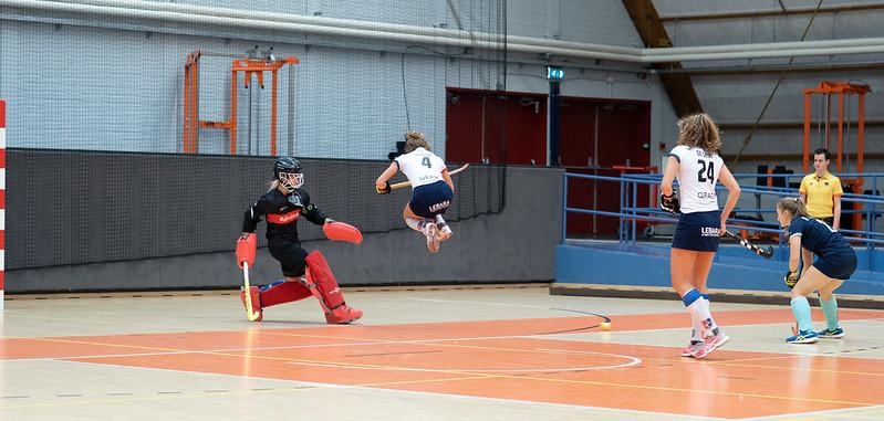 Anna de Geus (SCHC) kijkt toe hoe haar teamgenote over de bal heen springt.
